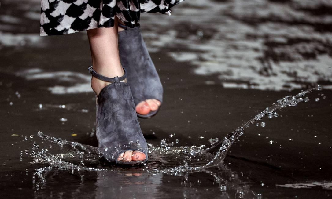 Chão propositalmente molhado segundos antes do início do desfile com baldes de água impôs desafio extra às modelos, que tiraram de letra em sandálias de salto alto de várias cores Yasuyoshi Chiba / AFP