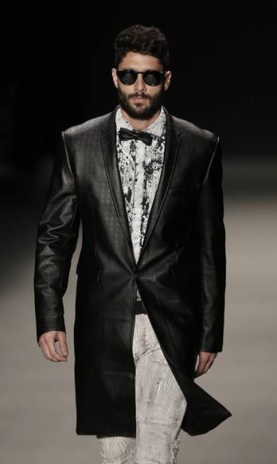 Modelos desfilaram usando óculos escuros o couro apareceu bastante, inclusive em gravata borboleta, detalhe do modelito feito com sobretudo preto Felipe Dana / AP