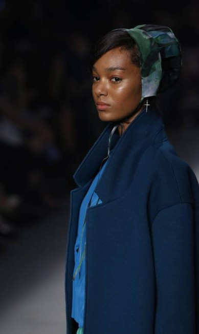 No perfil da modelo, percebe-se o detalhe da touca campesina usada nos looks femininos e do brinco em formato de cruz Mônica Imbuzeiro / Agência O Globo