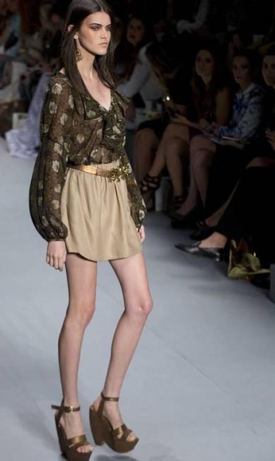 A blusa com manga comprida e babados foi combinada com saia bege também marcada na cintura Andre Penner / AP
