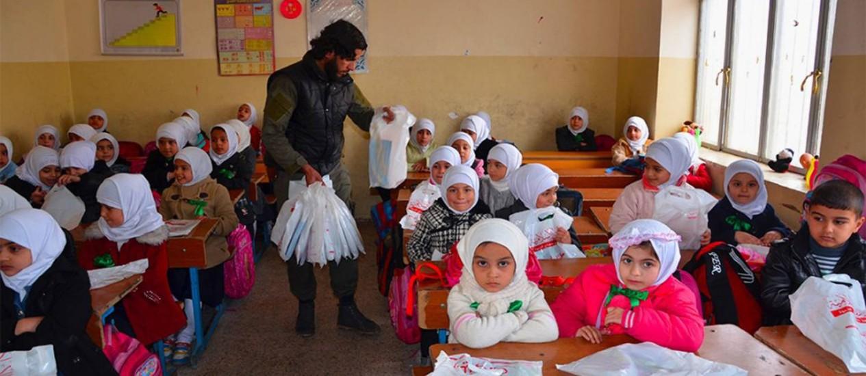 Educação radical. Militante do EI distribui itens de papelaria e outros presentes em escola iraquiana: capacidade do grupo de criar um Estado funcional e eficiência de guerra contra jihadistas é discutida por especialistas Foto: AP
