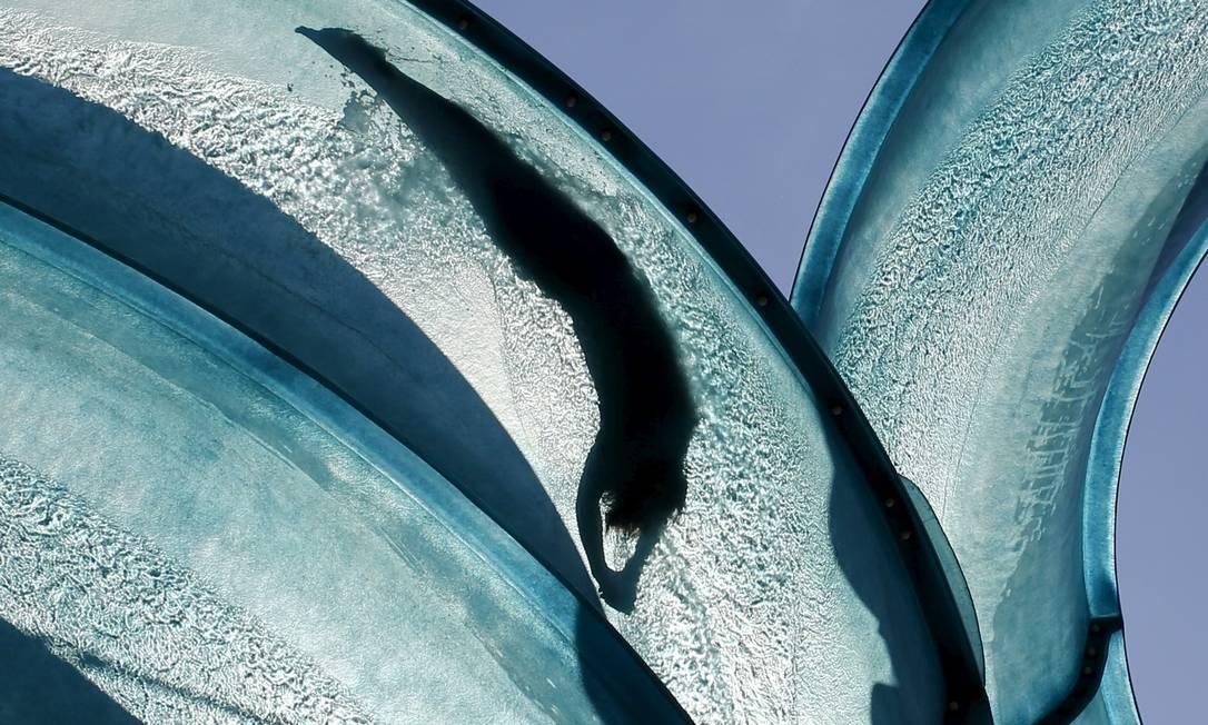 Uma silhueta compõe os traços suaves do registro que mostra uma pessoa deslizando em um tobogã em uma piscina pública em Viena, na Áustria, onde os termômetros marcam 37°C, podendo aumentar nos próximos dias LEONHARD FOEGER / REUTERS