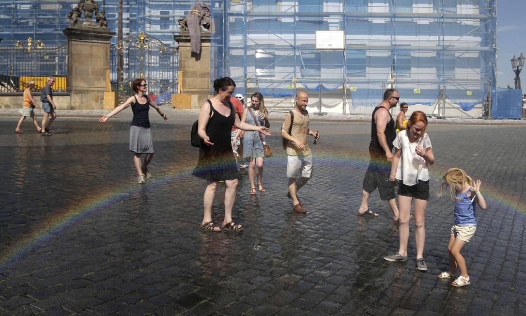 Em Praga, na República Tcheca, cidadãos dão um jeito de aproveitar a onda de calor, que elevou a temperatura a níveis recordes Petr David Josek / AP