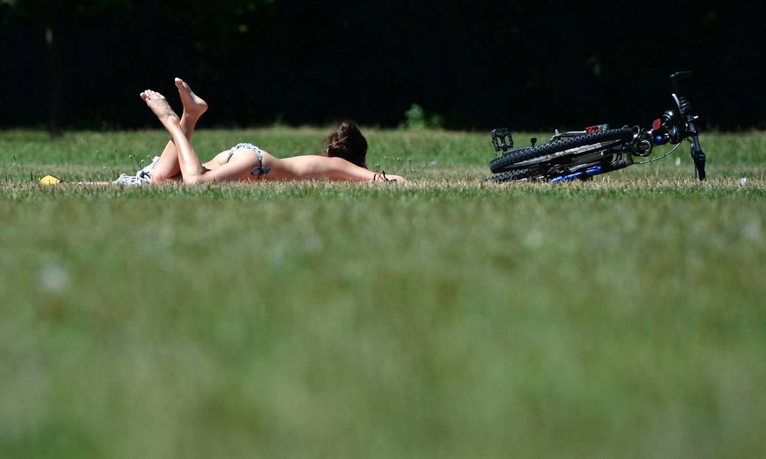 Mais acostumada com baixas temperaturas, uma jovem tira os trajes de banho do armário e descansa na grama do Jardim Inglês em Munique ANDREAS GEBERT / AFP