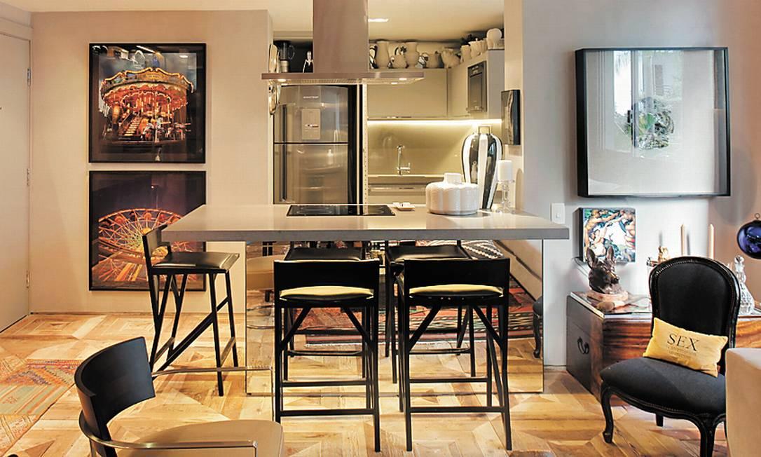 A cozinha aberta de Paola Ribeiro em São Paulo tem bancada que serve de mesa de jantar e bancos no lugar de cadeiras Divulgação