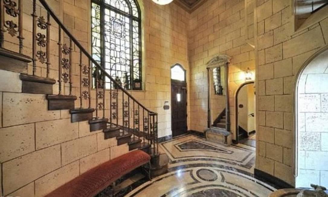 Piso de mármore e escada de ferro marcam a entrada da casa Divulgação MLS