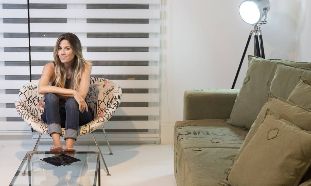A estilista Marcela Calmon na sala com o sofá de lona de caminhão Monica Imbuzeiro/ O Globo