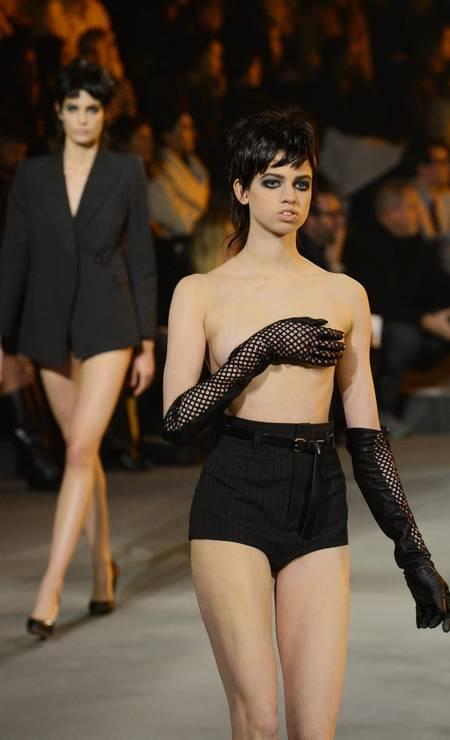 Com apenas duas temporadas no currículo, Lily McMenamy, filha da lendária supermodelo Kristen McMenamy, já colocou seus pés em passarelas preciosas, como as das grifes Chanel, Saint Laurent Paris e Marc Jacobs. No desfile de inverno 2013/2014 de Jacobs, inclusive, Lily, de apenas 18 anos, desfilou de topless. No entanto, escondeu seus seios estrategicamente com um dos braços Foto: STAN HONDA / AFP
