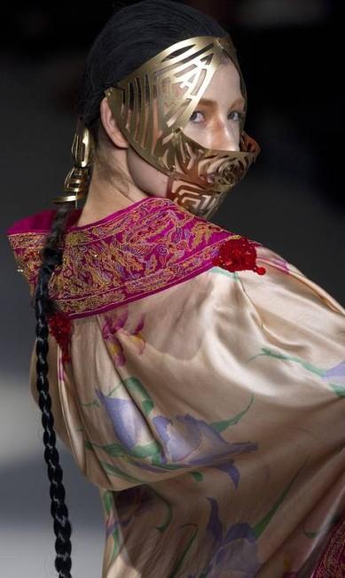Ele optou por apresentar os modelos com máscaras de metal e longas tranças Andre Penner / AP