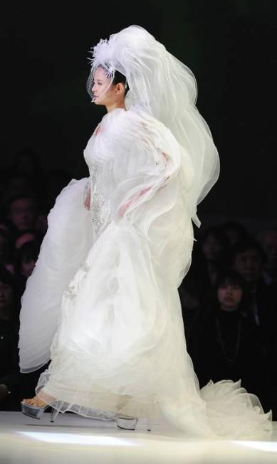 O véu cria uma proporção ampliada na parte de cima da roupa TORU YAMANAKA / AFP