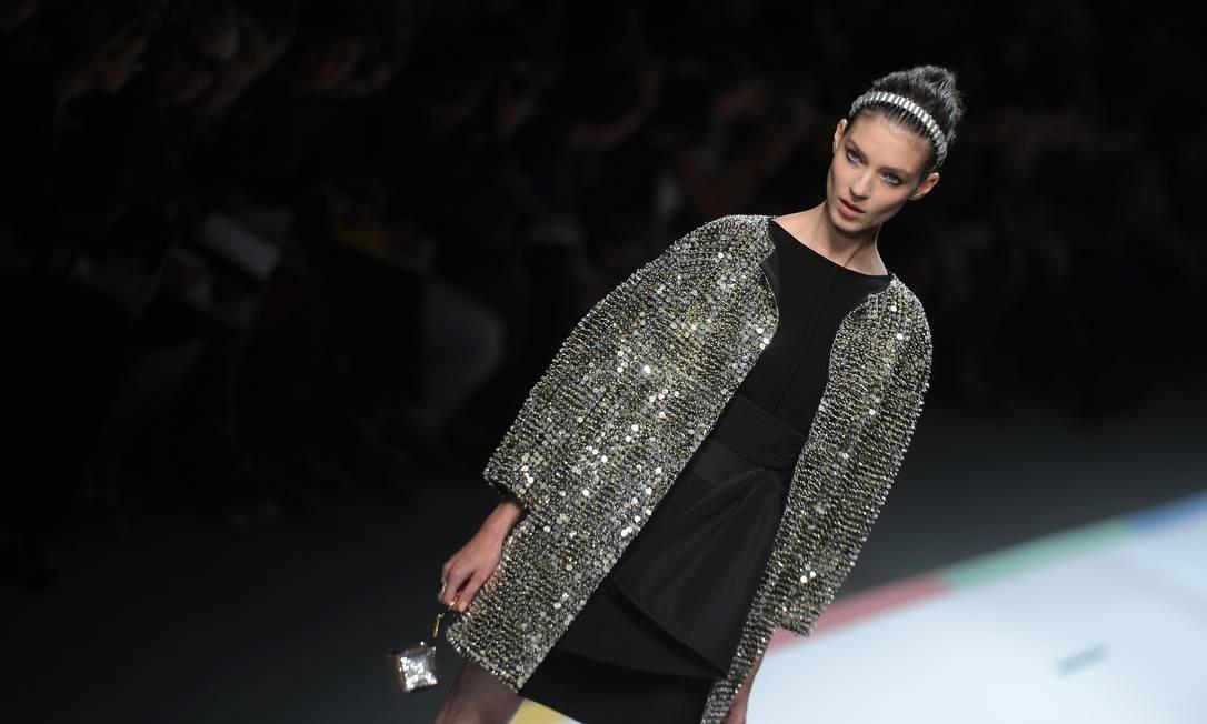 Sobre um vestido preto, o metalizado ganha um ar mais clássico. Destaque para a bolsinha em forma de dado da grife Foto: FILIPPO MONTEFORTE / AFP
