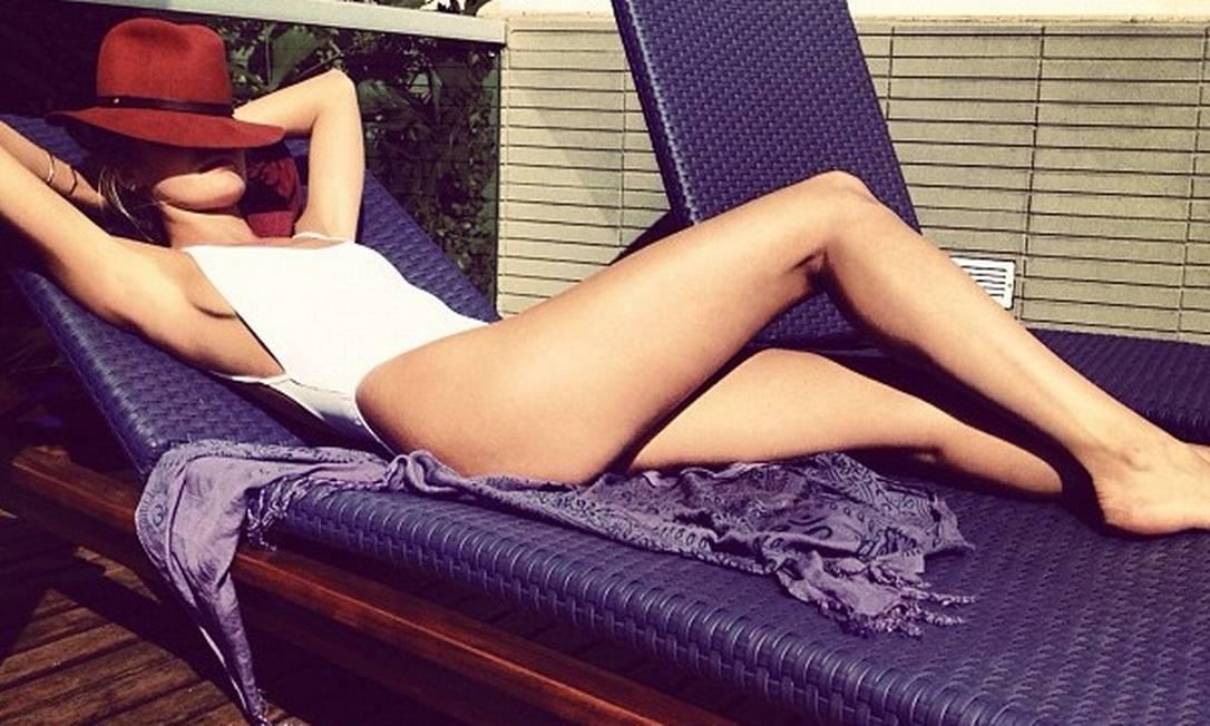 Em um domingo de folga, Candice posa de maiô branco e chapéu Rag & Bone. Na imagem, suas pernas são o centro das atenções Reprodução