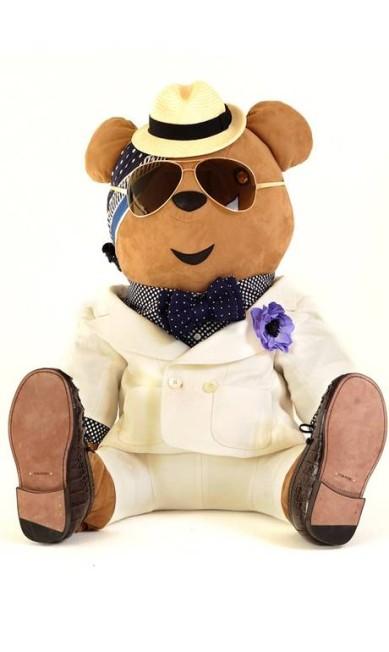 Tom Ford colocou o ursinho de terno, sapato chique, camisa, gravata borboleta, chapéu e óculos poderoso Reprodução