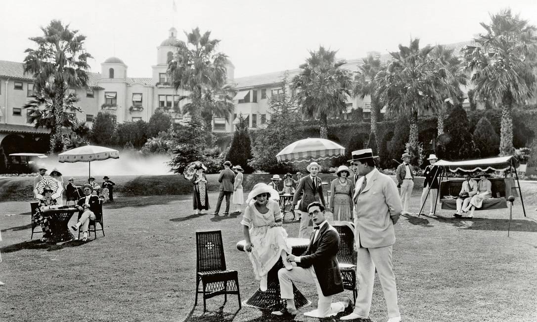 """Estrela do cinema mudo, Harold Lloyd (de joelhos) posa com seu elenco de apoio durante filmagem de """"A Sailor Made Man"""", em 1921 Cortesia do"""