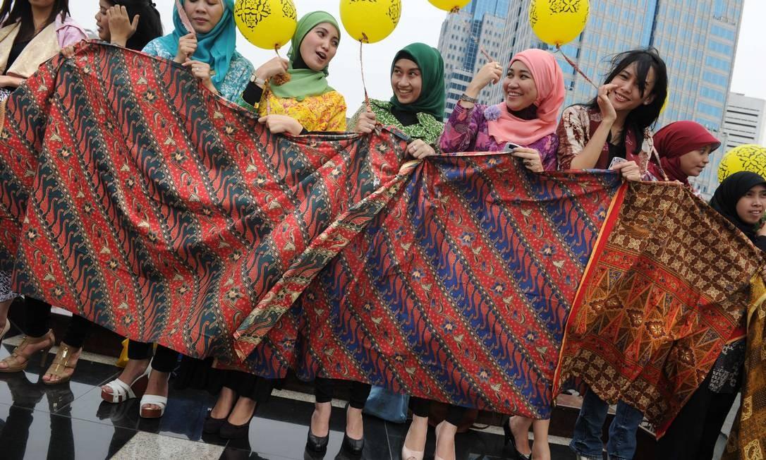 Funcionárias indonésias da empresa de telecomunicações Indosat exibem tecidos durante o Dia Nacional do batik, em Jacarta. A técnica de tingimento com cera é transmitida por gerações de artesãos ROMEO GACAD / AFP