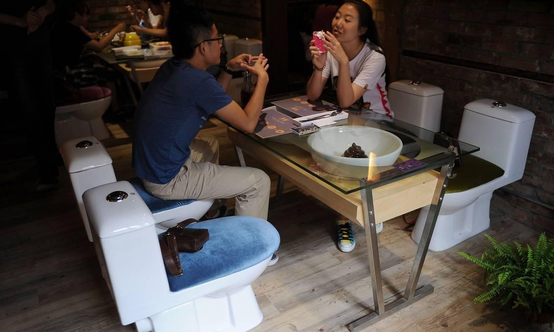 Em vez de cadeiras, vasos sanitários adaptados servem de assentos para os clientes PETER PARKS / AFP
