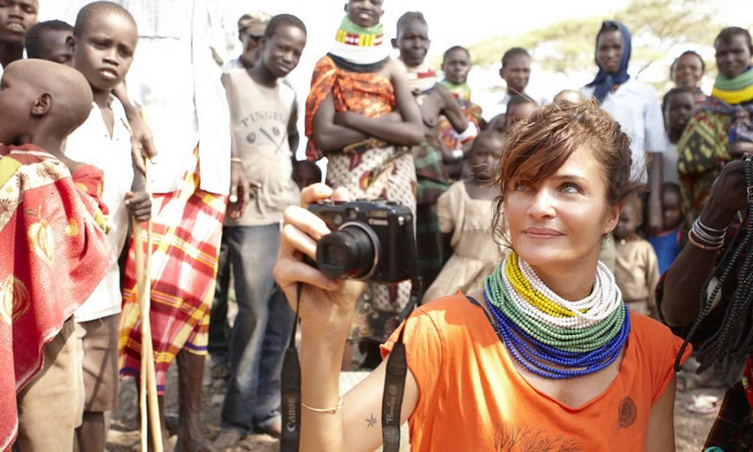 Vestindo os tradicionais colares quenianos, Helena tira fotos de uma vila Drew Doggett / Drew Doggett / Oxfam