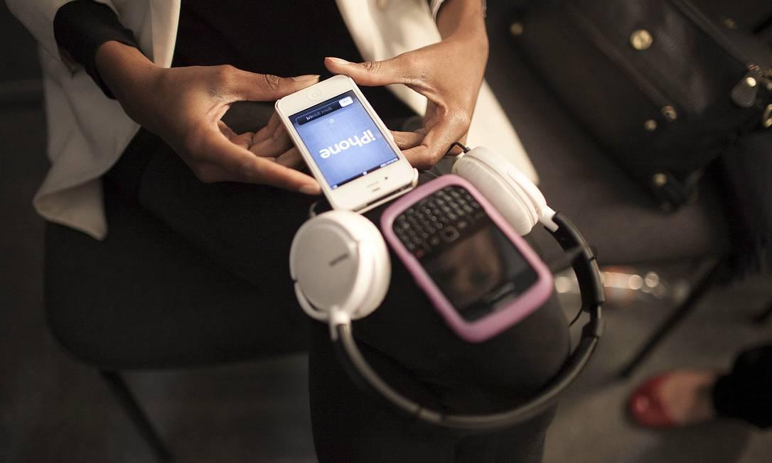 Indira Carvalho tem dois celulares (um blackberry e um iphone). O modelo da apple foi comprado na quarta-feria e ela pretende aposentar o BBerry. Ela sempre anda com um fone de ouvido enorme acoplado aos aparelhos para poder ouvir música nos backstages Leonardo Soare /O Globo