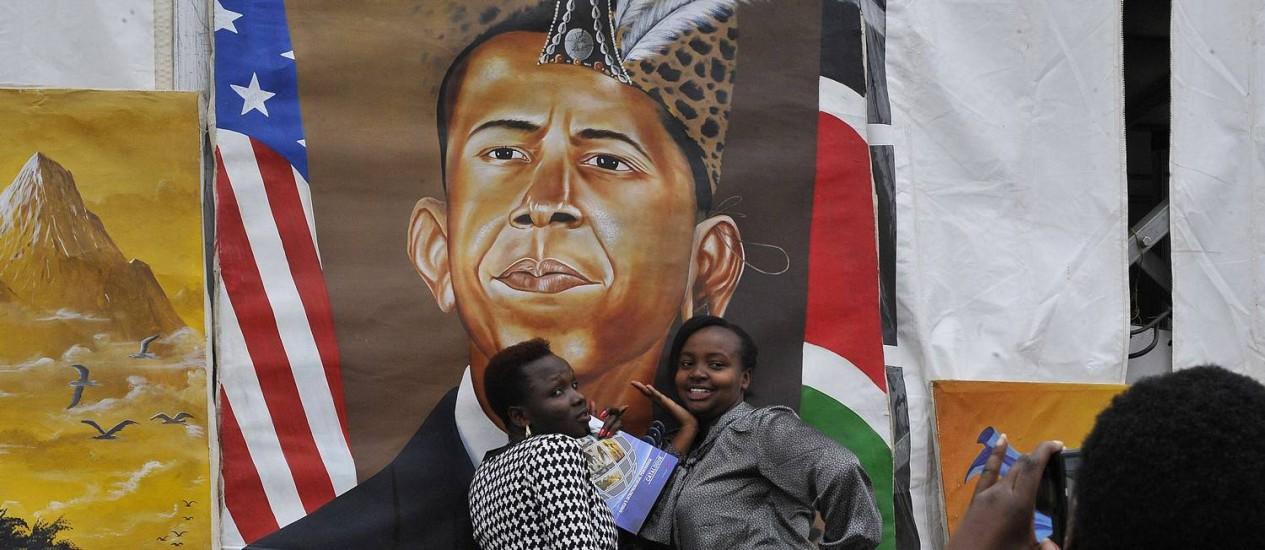 Africano. Mulheres posam ao lado de pintura mostrando Obama: terra da família paterna Foto: SIMON MAINA/AFP