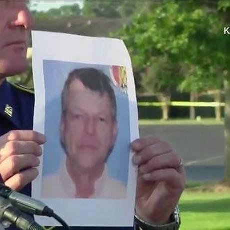 Policial mostra a foto de John Russell Houser, suspeito de matar duas pessoas em um cinema da Louisiana Foto: Reprodução da TV