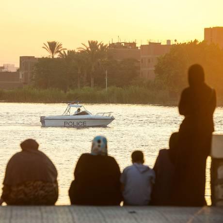 Parentes sentam-se na margem do Nilo à espera de notícias dos passageiros Foto: - / AFP