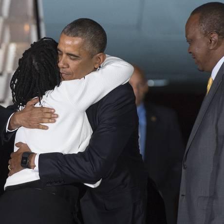 Observado pelo presidente Uhuru Kenyatta, Obama abraça sua meia-irmã Auma no aeroporto de Nairóbi Foto: SAUL LOEB / AFP