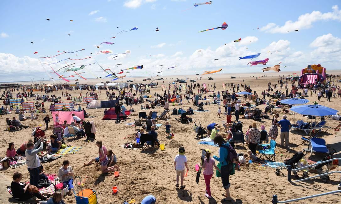 Público lotou areia da praia para acompanhar a exibição OLI SCARFF / AFP