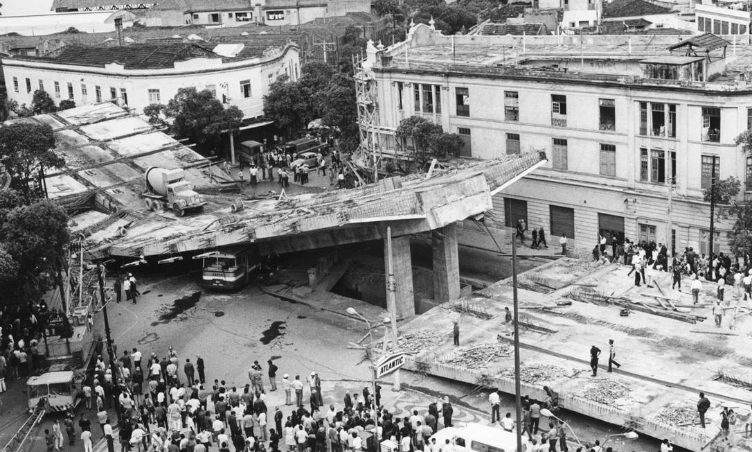 Tragédia no meio do caminho. Pessoas observam os escombros de um trecho do Elevado Paulo de Frontin que estava em construção e desabou em 20 de novembro de 1971, soterrando 20 carros, um ônibus e um caminhão. A queda deixou 26 mortos e 22 feridos Arquivo / O Globo