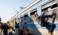 Travessia arriscada. Imigrantes tentam embarcar em trem na fronteira com a Sérvia