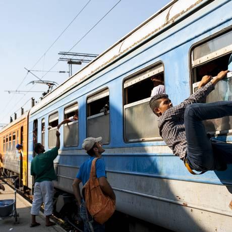 Travessia arriscada. Imigrantes tentam embarcar em trem na fronteira com a Sérvia Foto: ROBERT ATANASOVSKI / AFP/21-7-2015