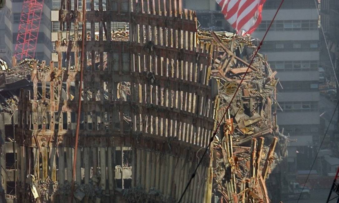 Destruição. Bandeira americana tremula sobre destroços do WorldTrade Center, um mês após os atentados de 11/9 Foto: Michael Conroy / Ap Photo
