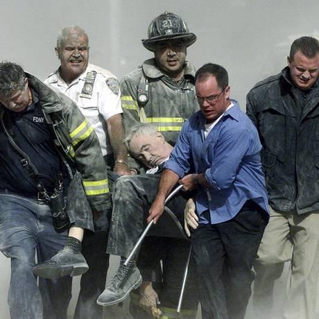 11 de setembro. Policiais e bombeiros removeram vítimas dos escombros após queda das torres gêmeas Foto: SHANNON STAPLETON / REUTERS