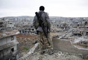 Curdo observa destroços na cidade síria de Kobani Foto: Uncredited / AP