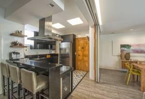 A cozinha, que pode integrar-se à sala, tem bancadas de granito preto e eletrodomésticos de aço Foto: Marcio Irala / Divulgação