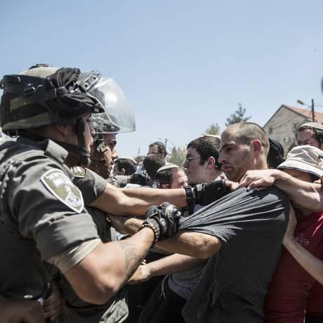 Colonos israelenses entram em confronto com agentes de polícia da Fronteira sobre demolição de prédio no assentamento de Beit El, perto da Cisjordânia Foto: Tsafrir Abayov / AP