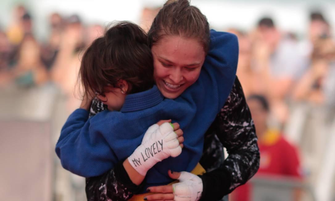 Rebeca, de 9 anos, ganha um abraço de Ronda Rousey no treino aberto do UFC na praia do Pepê, na Barra da Tijuca, Rio de Janeiro. Praticante de jiu jitsu, a menina foi chamada para dividir o tatame com a lutadora americana Pedro Kirilos / Agência O Globo
