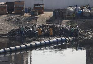 Garis removem lixo coletado no canal do Complexo da Maré, na Zona Norte do Rio Foto: Silvia Izquierdo / AP