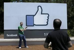 Homem posa com painel do Facebook na sede da empresa, na Califórnia: rede social é utilizada com frequência por 1,49 bilhão Foto: Jeff Chiu / AP