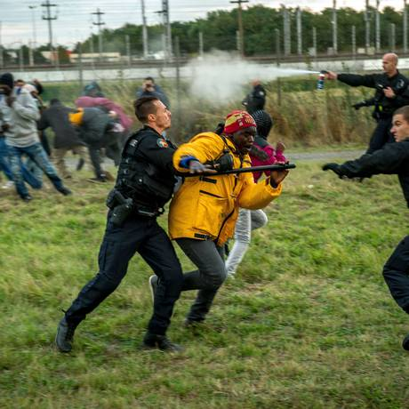 Em Coquelles, perto de Calais, policiais tentam impedir que imigrantes entrem no Eurotúnel para chegar à Inglaterra Foto: PHILIPPE HUGUEN / AFP