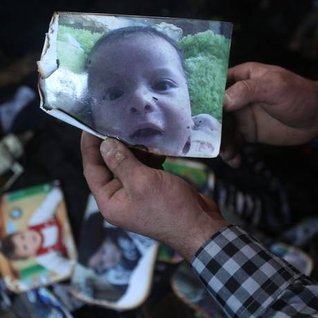 Um homem mostra uma imagem do bebê Ali Saad Dawabsha, morto em um incêndio criminoso em sua casa na Cisjordânia Foto: JAAFAR ASHTIYEH / AFP