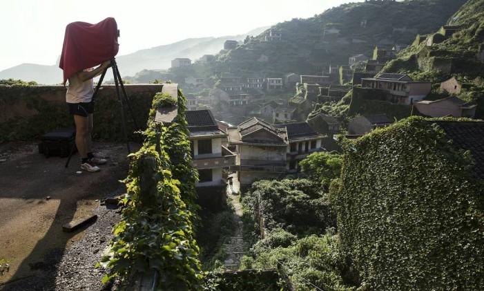 Fotógrafo no povoado abandonado de Houtouwan, na China. Foto: DAMIR SAGOLJ / REUTERS