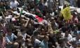 Corpo do jovem Laith al-Khaldi é carregado por milhares durante corjeto fúnebre no campo de refugiados de Jalazoun