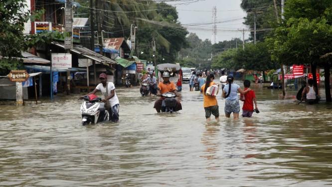 Moradores locais percorrem uma estrada inundada em Bago, 80 quilômetros a nordeste de Yangon Foto: Khin Maung Win / AP