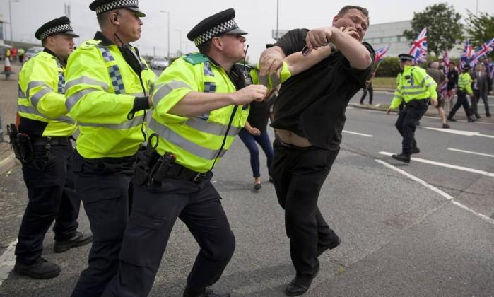Policiais detem manifestante durante caminhada em apoio aos imigrantes em Folkstone, ao sul da Inglaterra JUSTIN TALLIS / AFP