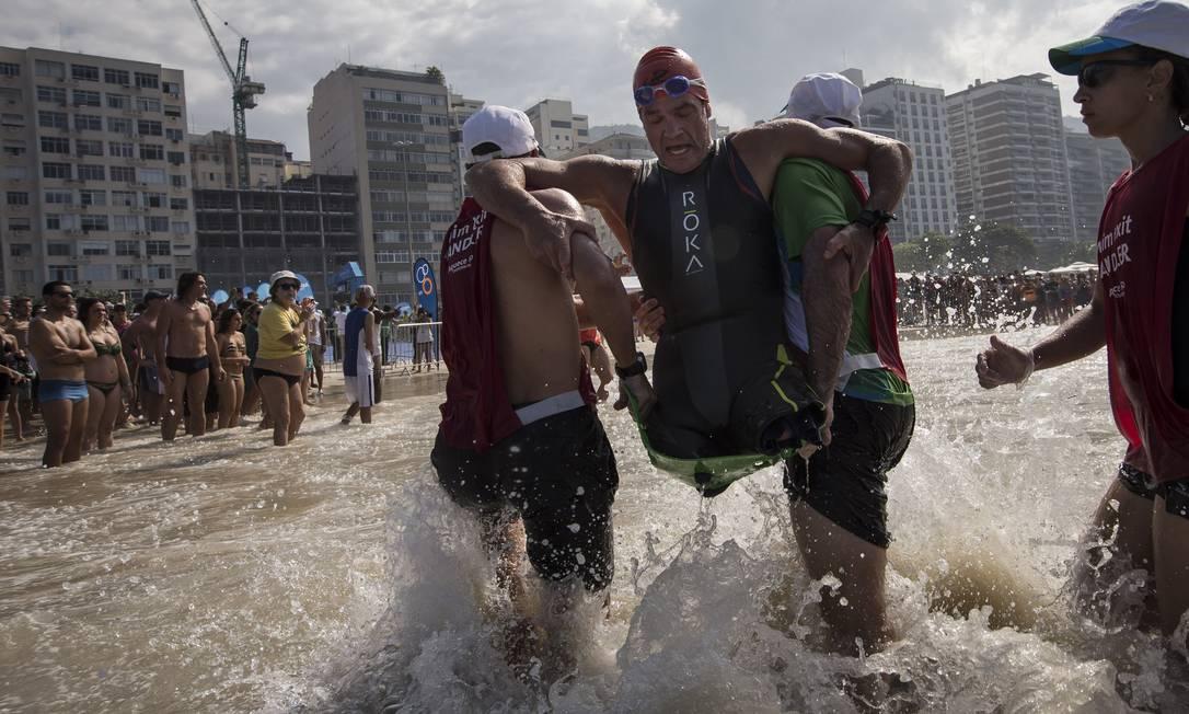 No sábado, Krige Schabort, dos Estados Unidos, é retirado da água após completar a prova de natação Felipe Dana / AP
