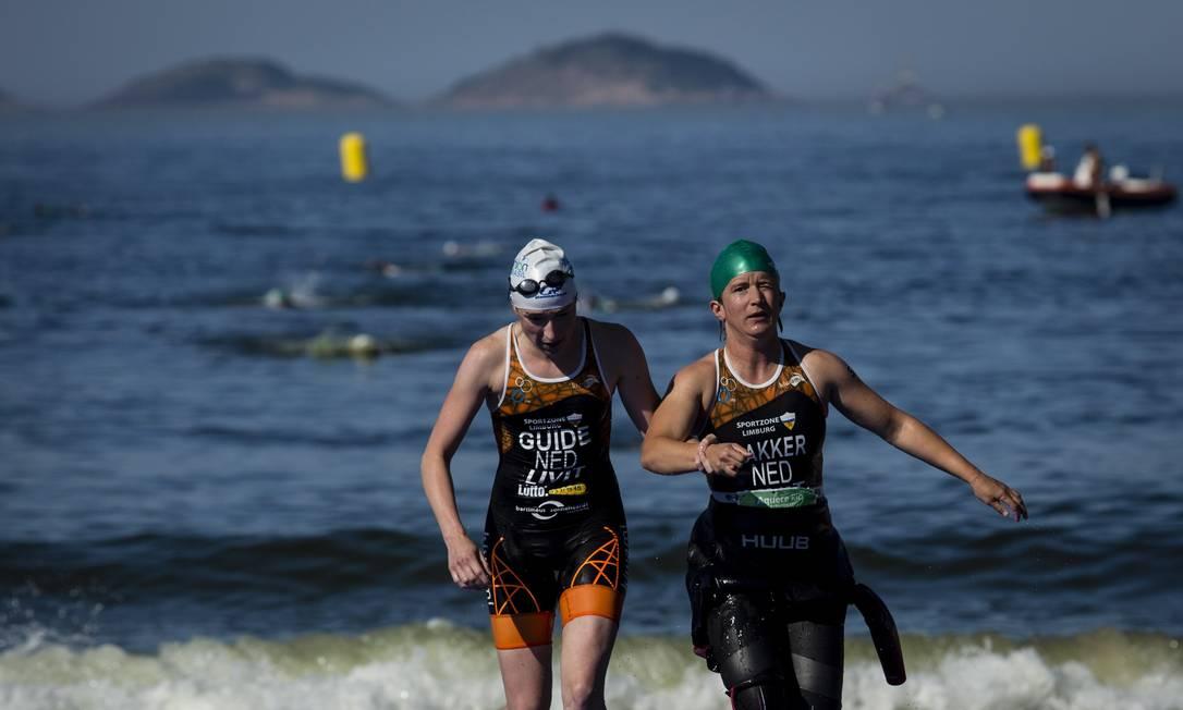 Atleta com deficiência visual recebe ajuda para sair do mar Fernando Lemos / Agência O Globo
