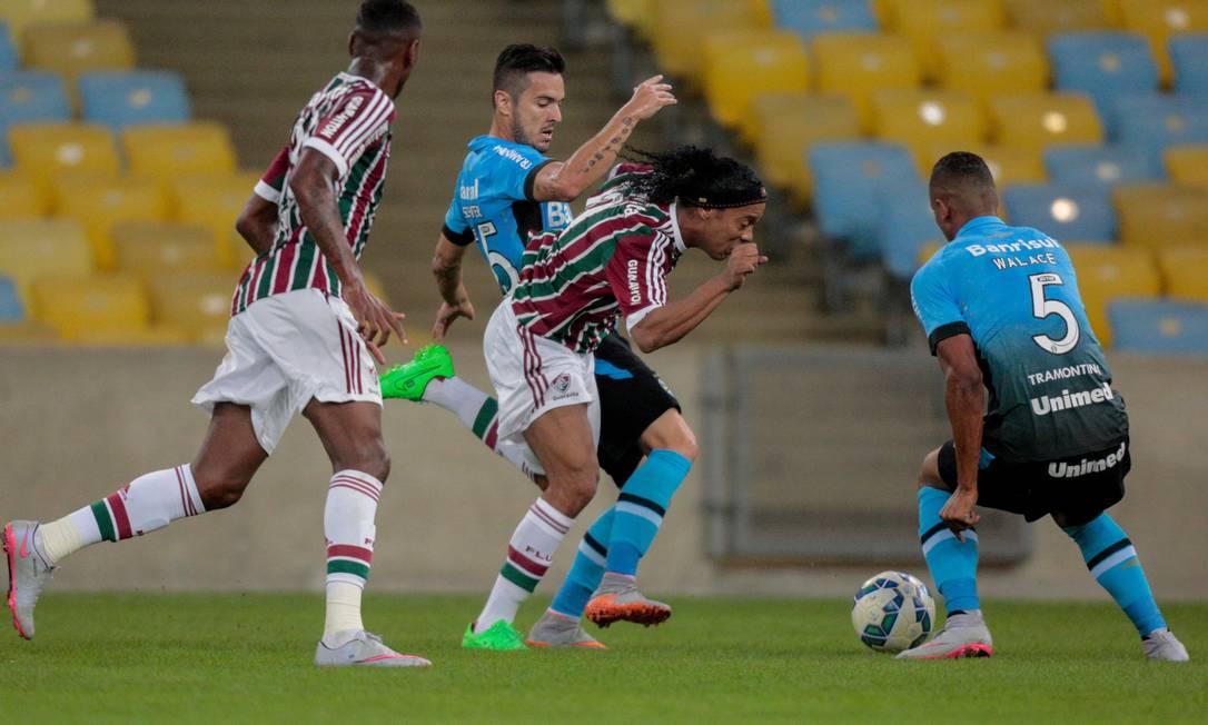 Ronaldinho tenta passar por dois marcadores do Grêmio Pedro Kirilos