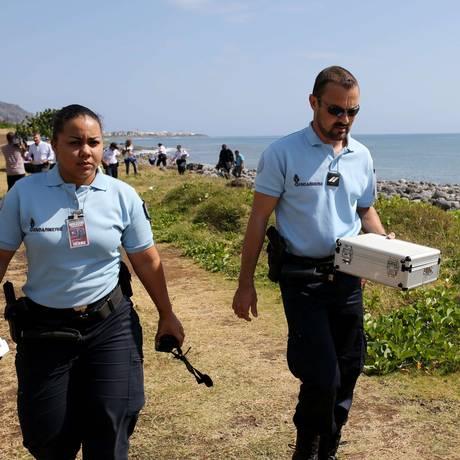 Agentes da polícia seguram caixa com destroços metálicos encontrados em uma praia em Saint-Denis, na Ilha francesa de Reunião Foto: RICHARD BOUHET / AFP