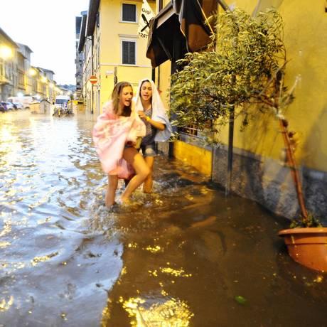 Duas meninas tentam atravessar rua inundada em Florença Foto: Maurizio Degl'Innocenti / AP