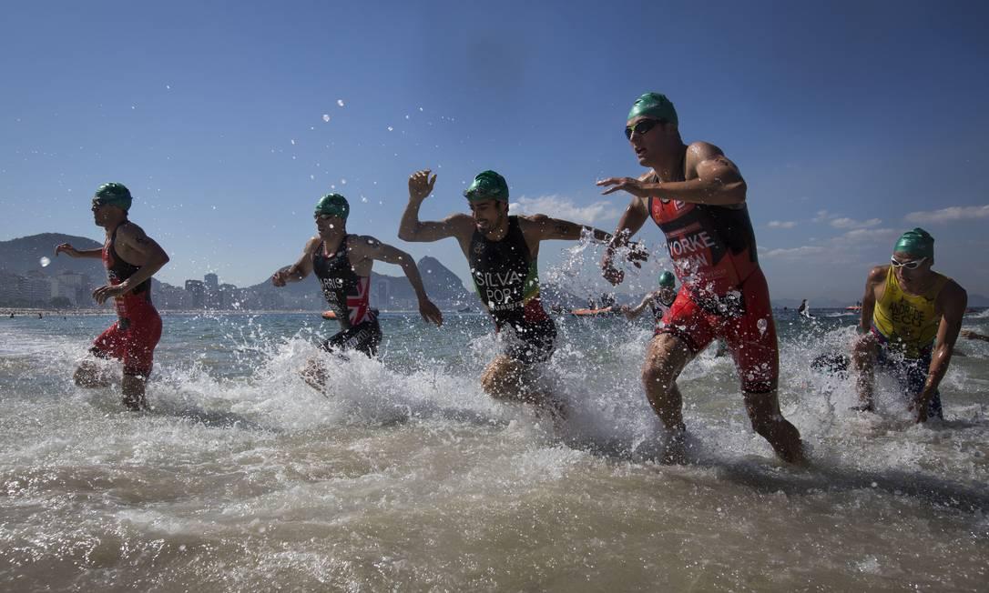 Triatletas deixam a água depois de completar a primeira etapa da prova que serviu como evento-teste para as Olimpíadas de 2016, neste domingo na praia de Copacabana Felipe Dana / AP
